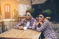 Asian and Arabic students couple in cafe Stock Images
