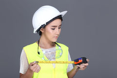 Asian Architect Engineer woman in white hard hat, safety vast, p. Beautiful Asian Architect Engineer woman in white hard hat, safety vast, protector glasses royalty free stock image