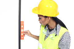 Asian Architect Engineer woman in yellow hard hat, safety vast. Equipment, thick gloves, protector glasses goggle and water level measure pole, studio lighting royalty free stock photography