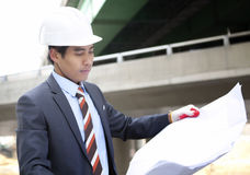 Asian architect on highway construction site. Young asian architect with blueprint on highway construction site Stock Images
