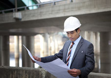 Asian architect on highway construction site. Young architect with blueprint on highway construction site Royalty Free Stock Images