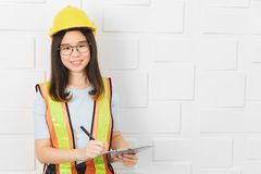 Asian architect lady at office. Young, beautiful, Asian architect wearing eyeglasses, yellow hardhat and yellow reflective safety vest, pen and clipboard in royalty free stock photo