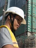 Asian architect profile looks down at plans with large housing project under construction in background Royalty Free Stock Photos