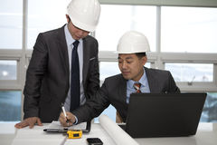 Asian architects working on planning. Two architects sitting at table and discussing a project in the office Royalty Free Stock Images
