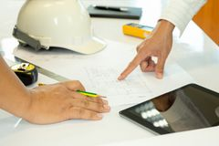 Asian architectuer working on plan hands pointing at bluepring sketch. royalty free stock photo