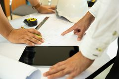Asian architectuer working on plan hands pointing at bluepring sketch. stock image