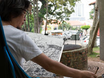 Asian Artist Sketches in Park. An Asian Artist sketches a scene in Melaka, Malaysia Stock Photography