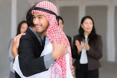 Asian and Arub business people greeting hug each other after pro. Ject deal project successful Stock Photos