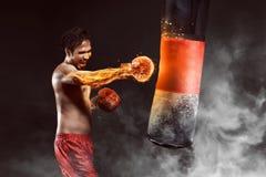 Asian athlete boxer punching a punching bag Stock Photography