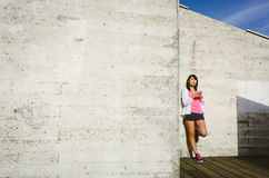 Asian athlete leaning against wall with smartphone Stock Image