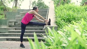 Asian Athlete women in sports clothing legs warming and stretching her arms to ready for running on street in urban city park. Healthy beautiful young Asian stock footage