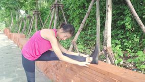 Asian Athlete women in sports clothing legs warming and stretching her arms to ready for running on street in urban city park. stock video footage