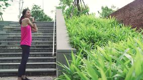 Asian Athlete women in sports clothing legs warming and stretching her arms to ready for running on street in urban city park. Healthy beautiful young Asian stock video