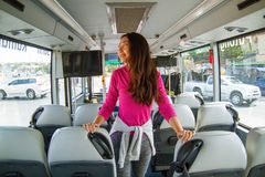 Asian attractive woman traveler with long hair standing in bus and enjoying the trip. stock images