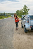 Asian and avto. Asian girl posing against the backdrop of the car on the road Royalty Free Stock Photo
