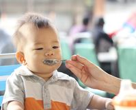 Asian baby being fed. Oriental baby eating at cafe being fed stock photo