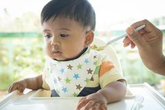 Asian baby bored with food. Cute asian baby bored with food stock images
