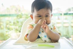 Asian baby bored with food. Cute asian baby bored with food stock photography