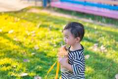 Asian baby boy drink with water bottle at outdoor playground, Stock Images