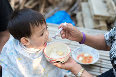 Asian baby boy feeding food by grand mother royalty free stock photography