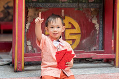 Asian baby boy hold red envelope or Ang-pow . The kid smiling because of feeling happiness from a Chinese new year gift royalty free stock image