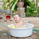 Asian baby boy outdoor bathing in the white bathtub . H Royalty Free Stock Images