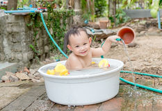 Asian baby boy outdoor bathing in the white bathtub . H Royalty Free Stock Image