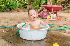 Asian baby boy outdoor bathing in the white bathtub . H Royalty Free Stock Photo