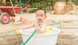 Asian baby boy outdoor bathing in the white bathtub . H Royalty Free Stock Photography