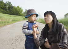Asian baby boy playing dandelion with his aunt Royalty Free Stock Images