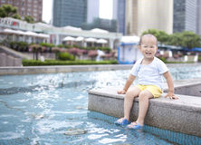Asian baby boy playing the water in a city pool. One asian baby boy playing water using foot Royalty Free Stock Photography