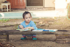 Asian baby boy reading tale book alone royalty free stock photo