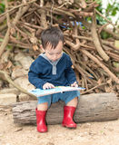 Asian baby boy  reading tale book ,The  Boy wear red boot sittin Royalty Free Stock Image