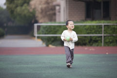 Asian baby boy running and holding a ball Royalty Free Stock Images