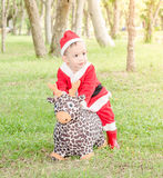 Asian baby boy in santa claus suit is ridding reindeer doll Stock Photos