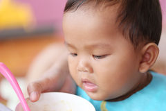 Asian baby boy to eating food in concept of health foods and nut. Rition for development and growth stock photos