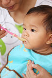Asian baby boy to eating food in concept of health foods and nut. Rition for development and growth stock photography