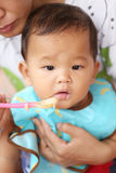Asian baby boy to eating food in concept of health foods and nut. Rition for development and growth stock photo