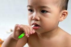 Asian baby brushing teeth closeup. 1 year old asian baby brushing teeth with a green toothbrush,staring left,closeup Stock Image
