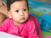 Asian baby crawling on the floor and looking straight. Royalty Free Stock Image