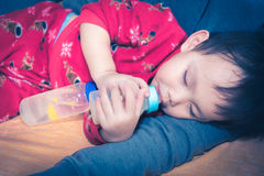 Asian baby drinking milk from bottle Stock Image