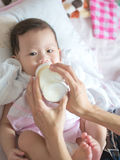 Asian baby eat milk from bottle. Royalty Free Stock Image