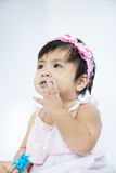 Asian baby is eating candy and wipe her dirty face selective focus at her hand royalty free stock images