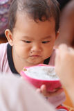 Asian baby eating a dragon fruit with happily. Royalty Free Stock Image