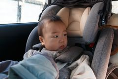Asian baby fastened with security belt in safety car seat. Asian little baby fastened with security belt in safety car seat stock photos