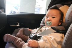 Asian baby fastened with security belt in safety car seat. Asian little baby fastened with security belt in safety car seat stock images