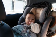 Asian baby fastened with security belt in safety car seat. Asian little baby fastened with security belt in safety car seat stock image