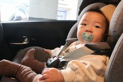 Asian baby fastened with security belt in safety car seat. Asian little baby fastened with security belt in safety car seat royalty free stock image