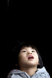 Asian baby girl. Portrait of little baby girl in curiosity isolated in dark background Royalty Free Stock Image