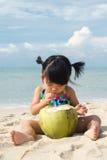 Asian baby girl on beach. Asian baby girl drinking coconut fruit on beach Stock Photos